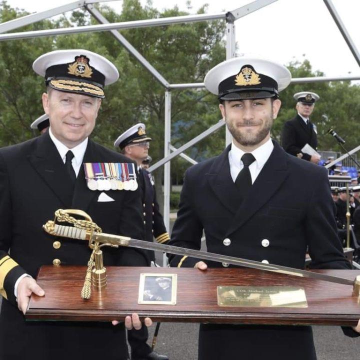 Photograph of Lt Marr receiving an award from a Rear Admiral.